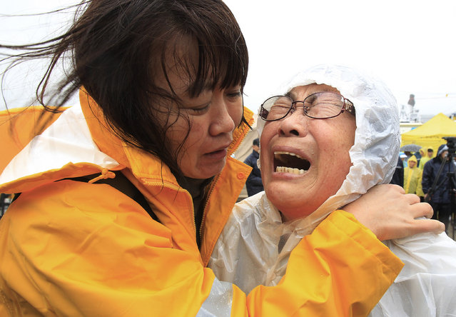 Relatives of a passenger aboard a sunken ferry weep as they wait for news on the rescue operation, at a port in Jindo, South Korea, Thursday, April 17, 2014. Strong currents, rain and bad visibility hampered an increasingly anxious search Thursday for more than 280 passengers still missing a day after their ferry flipped onto its side and sank in cold waters off the southern coast of South Korea. (Photo by Ahn Young-joon/AP Photo)