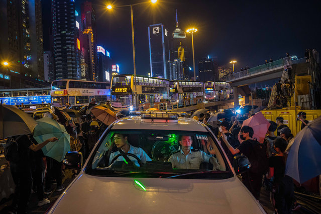 "Protestors shine a laser light into a police vehicle during a protest in the Causeway Bay district on August 04, 2019 in Hong Kong, China. Pro-democracy protesters have continued rallies on the streets of Hong Kong against a controversial extradition bill since 9 June as the city plunged into crisis after waves of demonstrations and several violent clashes. Hong Kong's Chief Executive Carrie Lam apologized for introducing the bill and declared it ""dead"", however protesters have continued to draw large crowds with demands for Lam's resignation and completely withdraw the bill. (Photo by Billy H.C. Kwok/Getty Images)"