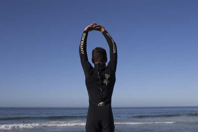 In this  May 21, 2015 photo, Gabriel de Lima, 13, stretches before surfing at Sao Conrado beach in Rio de Janeiro, Brazil. Not long ago, many of these kids were begging on the streets or engaged in crime, but two surf schools serving youth from Rio's largest slum, Rocinha, have helped change that. (Photo by Felipe Dana/AP Photo)