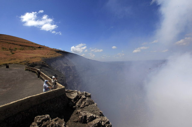 Tourists stand at a lookout as steam rises from the Santiago Crater at Masaya Volcano National Park on Earth Day, near Managua April 22, 2014. (Photo by Oswaldo Rivas/Reuters)