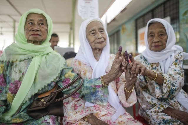 Malaysian siblings Soyong Labor, 92, (R) Khairiah Labor, 84, (C) and Enong Labor, 82, (L) pose for photos showing their ink marked fingers after casting their votes at a polling station in Kuching, Sarawak, Malaysia, 07 May 2016. More than one million people participated in Sarawak's biggest state elections on 07 May 2016. A total of 82 seats are being contested in the Barisan Nasional party (The National Front Party) stronghold as Sarawak Chief Minister Adenan Satem is leading the ruling coalition. (Photo by Fazry Ismail/EPA)
