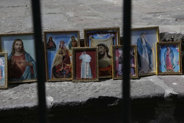 This June 14, 2015 photo shows framed images of Catholic icons on a street in downtown Quito, Ecuador. Pope Francis will encounter on his South American tour indigenous people whose traditions date back centuries to even before European priests brought Christianity to the New World. (Photo by Dolores Ochoa/AP Photo)