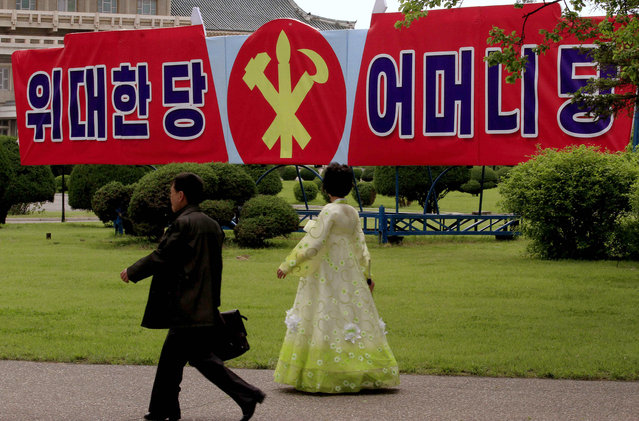 """North Koreans walk past a slogan which reads """"Great Party, Mother Party"""" along a sidewalk on Wednesday, May 4, 2016, in Pyongyang, North Korea. North Korea is preparing to hold a once-in-a-generation congress of its ruling party that is intended to rally the nation behind leader Kim Jong Un and could provide an important glimpse into Kim's plans for the country's economy and military. (Photo by Kim Kwang Hyon/AP Photo)"""