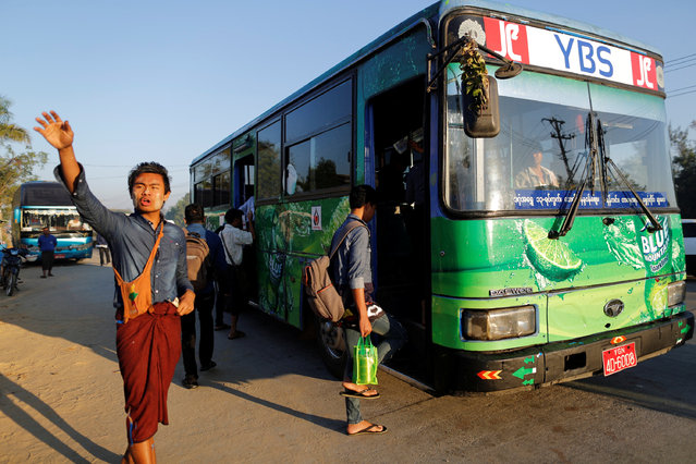 An assistant driver waves to passengers in Yangon, Myanmar January 16, 2017. (Photo by Soe Zeya Tun/Reuters)