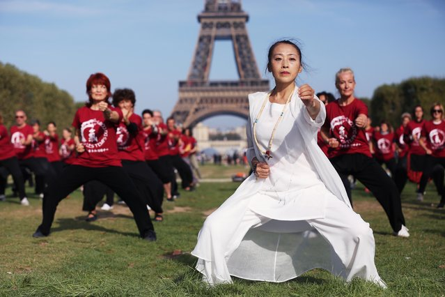 People practice Qigong, a traditional Chinese practice to cultivate and balance the body's inner energy, at Champs de Mars in Paris, France on September 14, 2019. (Photo by Gao Jing/Xinhua News Agency)