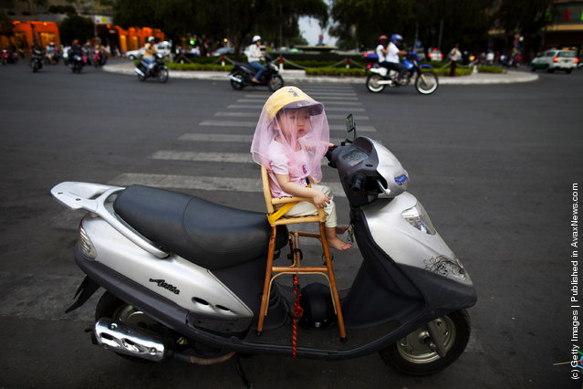 A Vietnamese girl sits on her father's new motorcycle