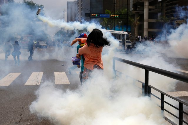 An anti-government protester throws a gas canister back at the police during a protest against President Nicolas Maduro's government in Caracas, May 8, 2014. Venezuelan authorities arrested hundreds of youth activists who had spent weeks in camps set up in public spaces as part of protests. (Photo by Carlos Garcia Rawlins/Reuters)