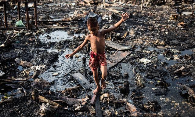 A boy walks through debris after fire razed the Mirpur slum in Dhaka, Bangladesh on August 20, 2019. (Photo by Md Rakibul Hasan/Pacific Press via ZUMA Wire/Rex Features/Shutterstock)