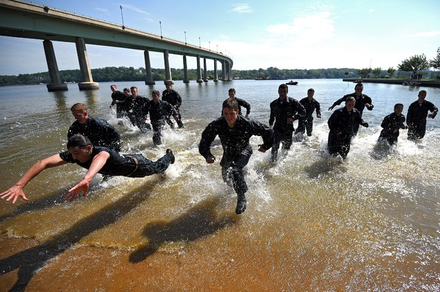 Plebes race to the sand at the wet and sandy station during the annual Sea Trials training exercise. (Photo by Patrick Smith/Getty Images)
