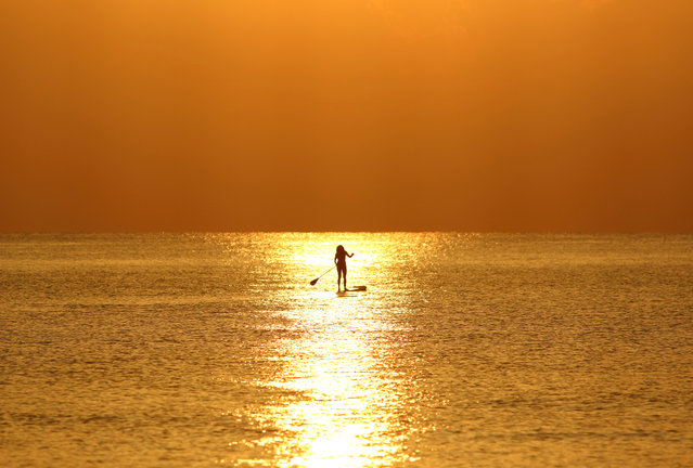 A woman paddles on a stand-up board during sunrise in a beach in Larnaca, Cyprus on September 15, 2019. (Photo by Yiannis Kourtoglou/Reuters)