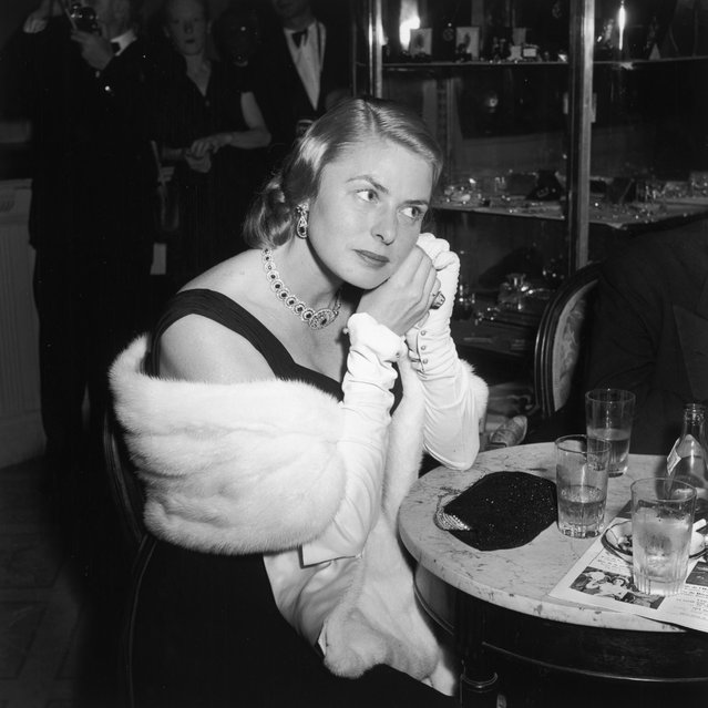Swedish-born actress Ingrid Bergman adjusts an earring as she sits at a cocktail table at the Cannes Film Festival, May 1956, in France. (Photo by Hulton Archive/Getty Images)