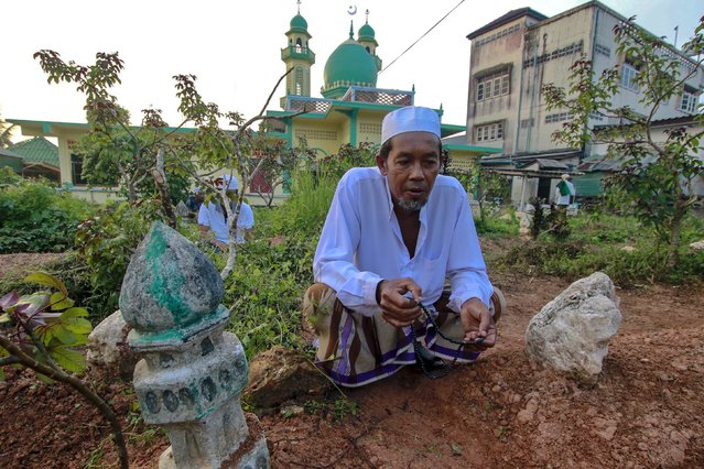 A Muslim man recites prayer at relatives' graves on Eid Al-Fitr in Yala province, Thailand, July 17, 2015. (Photo by Surapan Boonthanom/Reuters)