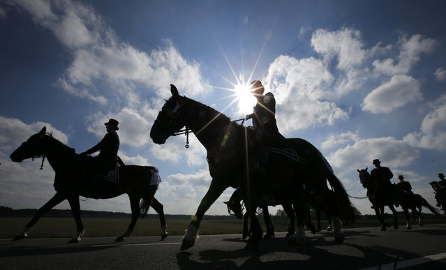 Men of the German Slavic minority Sorbs, dressed in traditional clothes, ride horses during a ceremonial parade near the village of Ralbitz, northeast of Dresden, April 20, 2014. More than 1,000 horse riders took part in several parades to mark the resurrection of Jesus Christ on Easter Sunday. (Photo by Fabrizio Bensch/Reuters)