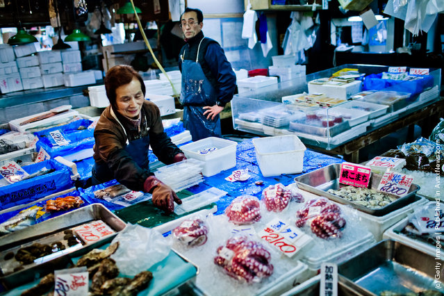 A woman starts to pack away seafood at the end of trade at the Tsukiji fish market