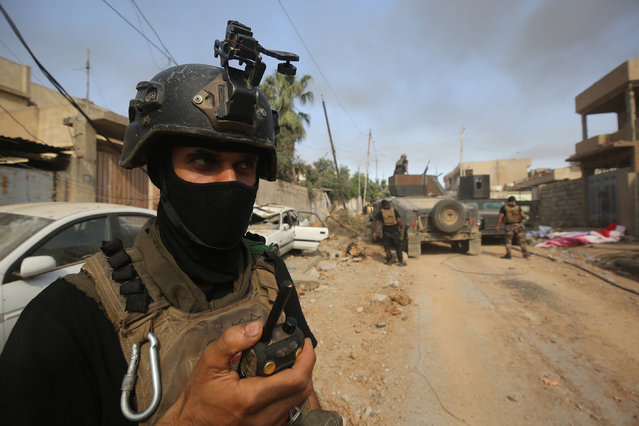 Members of the Iraqi Counter-Terrorism Service (CTS) take position as they advance towards Mosul's Al-Oraibi western district on May 14, 2017, during the ongoing offensive to retake the city from Islamic State (IS) group fighters. (Photo by Ahmad Al-Rubaye/AFP Photo)