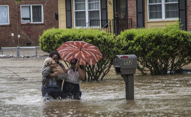 Nautica Jackson, left, and Aniya Ruffin walk through floodwaters with their dog as water threatened to enter their home in Raleigh, N.C. Tuesday, April 25, 2017.  The National Weather Service had flood watches and warnings in effect in the eastern half of the state Tuesday morning after storms dumped several inches of rain in the Raleigh area. (Photo by Travis Long/The News & Observer via AP Photo)