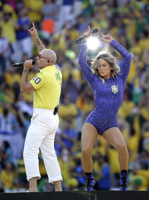 Rapper Pitbull, left, and Brazilian singer Claudia Leitte perform during the opening ceremony ahead of the group A World Cup soccer match between Brazil and Croatia, the opening game of the tournament, in the Itaquerao Stadium in Sao Paulo, Brazil, Thursday, June 12, 2014. (Photo by Felipe Dana/AP Photo)