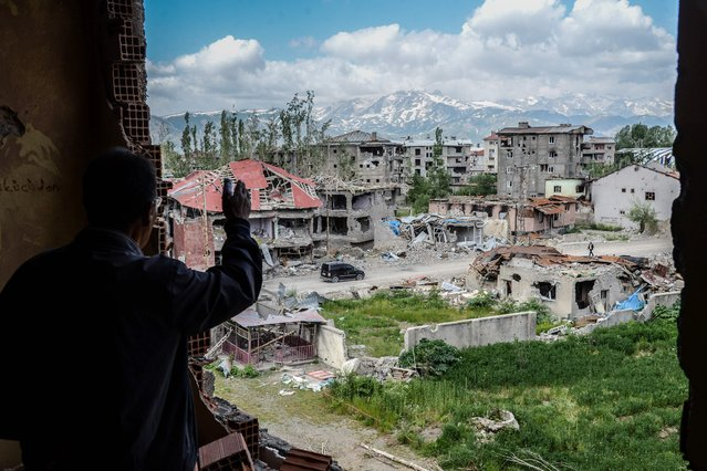 A man reacts from his balcony as he sees damaged buildings after heavy fightings between Turkish government troops and Kurdish fighters during the curfew in the southeastern Turkey Kurdish town of Yuksekova, near the border with Iraq and Iran, on May 30, 2016. (Photo by Ilyas Akengin/AFP Photo)