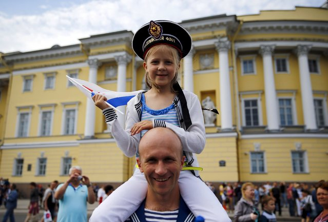 """People take part in celebrations for Navy Day of Russia in St. Petersburg, Russia, July 26, 2015. The girl wears a navy service cap with words reading """"Baltic fleet"""". (Photo by Reuters/Stringer)"""
