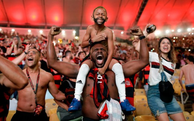 Flamengo soccer fans cheer a goal scored by Gabriel against Argentina's River Plate in the Copa Libertadores final match, broadcast on a giant screen at a watch party at the Macarena Stadium, in Rio de Janeiro, Brazil, Saturday, November 23, 2019. The first single-match final will be played in front of more than 65,000 fans at Lima's Monumental Stadium. The match was originally scheduled for Santiago's National Stadium, but it was moved because of street protests in Chile. (Photo by Silvia Izquierdo/AP Photo)