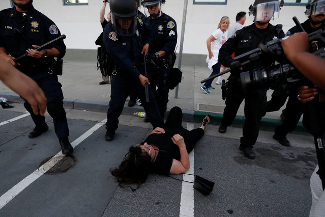 A woman falls as police officers move the line during a demonstration against Republican U.S. presidential candidate Donald Trump outside his campaign event in San Jose, California, U.S. June 2, 2016. (Photo by Stephen Lam/Reuters)
