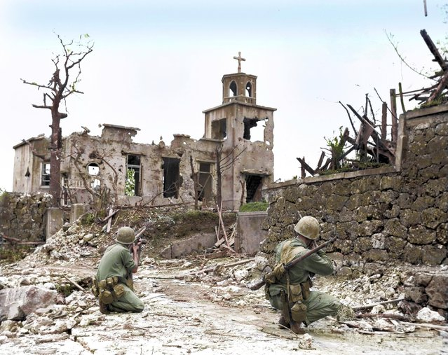 While a patrol moves in from the rear, two United States Marines cover a Japanese sniper hiding in a church, below Shuri Castle on Okinawa, 1945. (Photo by Royston Leonard/Mediadrumworld)
