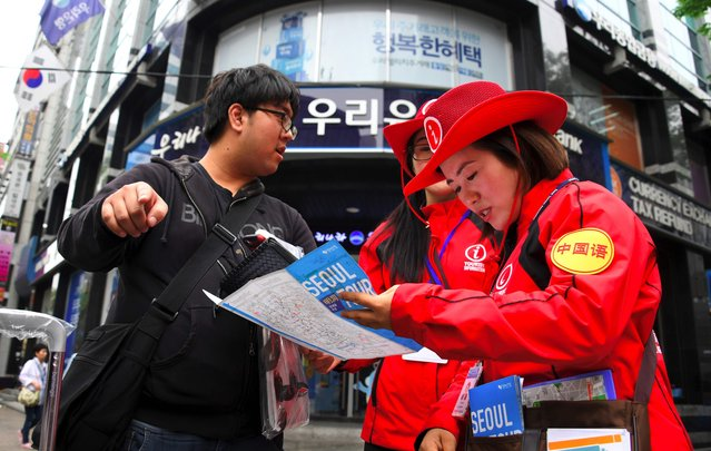 South Korean tourist information helpers (red) guide tourists in the popular Myeongdong shopping district in Seoul on April 25, 2017. South Korea's tourist industry has been hammered by China's boycott over the deployment of US missile defence system, with visitor numbers from the Asian giant plummeting 40 percent in March, statistics showed. (Photo by Jung Yeon-Je/AFP Photo)