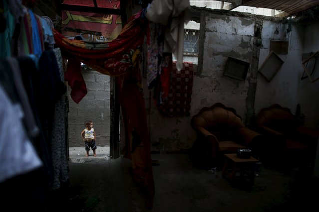 A Palestinian boy stands outside his family's house during power cut at Shatti (beach) refugee camp in Gaza City July 23, 2015. (Photo by Mohammed Salem/Reuters)