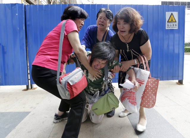 Bao Lanfang (C), whose son, daughter-in-law and 3-year-old granddaughter were aboard Malaysia Airlines flight MH370, kneels down in front of media before she and other family members express their demands to Malaysia Airlines outside its Beijing office August 6, 2015. About a dozen grieving family members outside the Malaysia Airlines Beijing office on Thursday demanded more information and the visa to travel to Reunion Island. (Photo by Jason Lee/Reuters)
