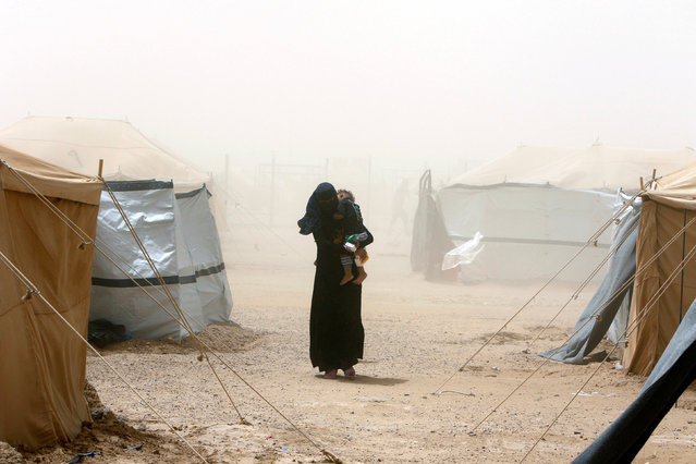 A woman, who fled from Falluja because of Islamic State violence, carries her child during a dust storm at a refugee camp in Ameriyat Falluja, south of Falluja, Iraq, June 16, 2016. (Photo by Ahmed Saad/Reuters)