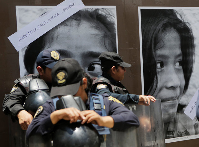 Riot police officers stand guard next to posters with images of children, which are part of an artistic project by Renaissance Foundation IAP featuring children rescued from the city's streets, as protesters (not pictured) from the National Coordination of Education Workers (CNTE) teachers' union arrive in Mexico City to attend a march against President Enrique Pena Nieto's education reform, Mexico June 16, 2016. (Photo by Henry Romero/Reuters)