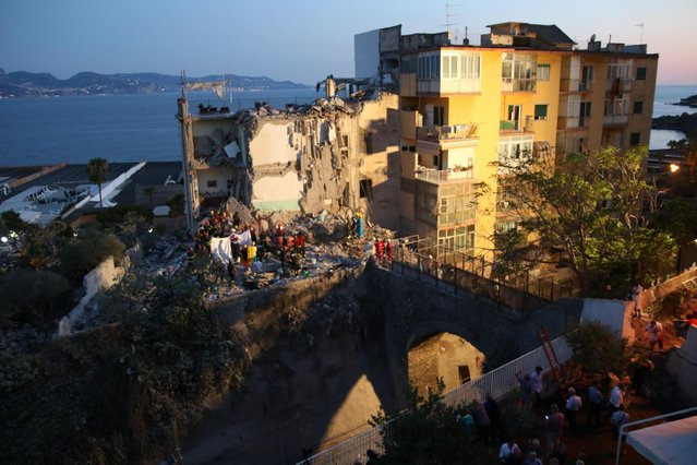 Rescuers work amid the rubble of a building that collapsed in Torre Annunziata, near Naples, southern Italy, Friday, July 7, 2017. A five-story apartment block collapsed early Friday near the southern Italian city of Naples, and authorities were digging by hand to find anyone who may have been trapped. (Photo by Ciro Fusco/ANSA via AP Photo)