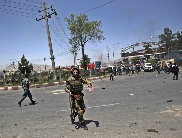An Afghan National Army soldier asks public to leave after a car bomb blast, at the entrance gate to the Kabul airport in Afghanistan August 10, 2015. (Photo by Ahmad Masood/Reuters)