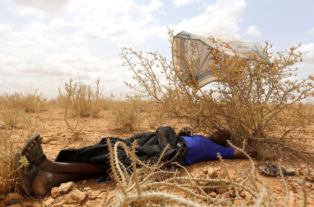 An internally displaced man who fled flooding of the overflowed Shabelle river rests under a shade as he waits to receive relief assistance near Baledweyne town central Somalia, June 22, 2016. (Photo by Feisal Omar/Reuters)