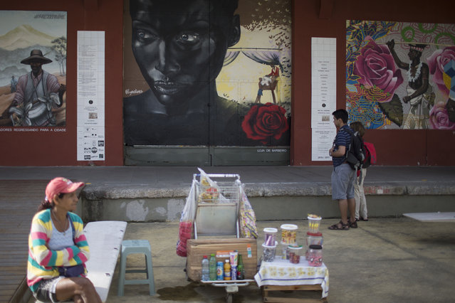 """In this July 9, 2017 photo, tourists look at murals in the renovated port area in Rio de Janeiro, Brazil. A new app called """"Museum of Yesterday"""" seeks to educate visitors about the history and role of Rio de Janeiro's revitalized port in colonization, slavery and even recent corruption investigations. (Photo by Renata Brito/AP Photo)"""