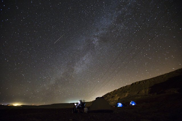 A meteor streaks across the sky in the early morning as people watching during the Perseid meteor shower in Ramon Carter near the town of Mitzpe Ramon, southern Israel, August 13, 2015. The Perseid meteor shower is sparked every August when the Earth passes through a stream of space debris left by comet Swift-Tuttle. (Photo by Amir Cohen/Reuters)