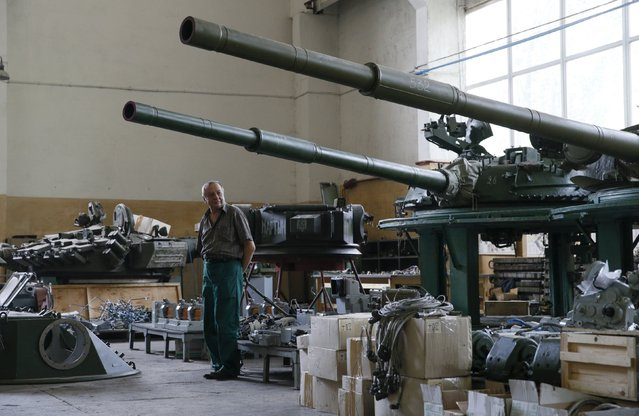 An employee stands near turrets as armored vehicles are repaired at the Kiev armored plant, Ukraine, August 14, 2015. (Photo by Valentyn Ogirenko/Reuters)