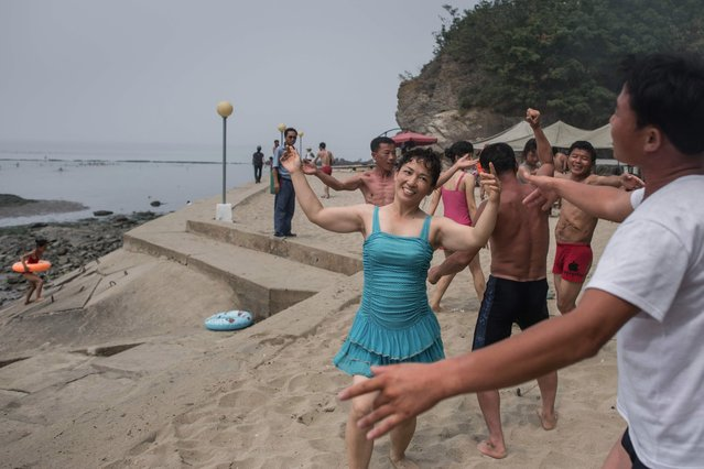 A photo taken on July 22, 2017 shows beach- goers dancing at the West Sea Barrage beach outside the coastal city of Nampo, southwest of Pyongyang. (Photo by Ed Jones/AFP Photo)