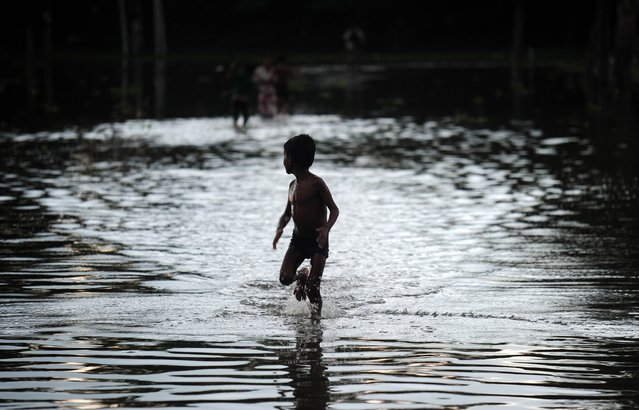 An Indian boy plays along a waterlogged street in Allahabad on July 19, 2014. The southwest monsoon covered the entire country on July 17, two days behind the normal schedule. (Photo by Sanjay Kanojia/AFP Photo)
