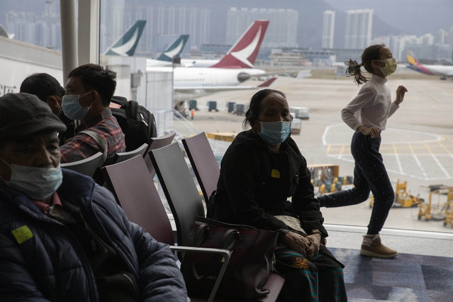 A child runs past passengers wearing masks waiting for their flight in Hong Kong on Sunday, February 9, 2020. China's virus death toll rose above 800, passing the number of fatalities in the 2002-2003 SARS epidemic, but fewer new cases were reported in a possible sign its spread may be slowing as other nations step up efforts to block the disease. (Photo by Ng Han Guan/AP Photo)