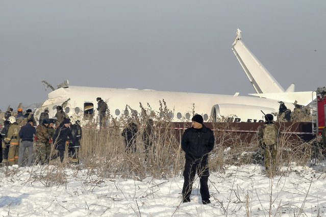 Police guard as rescuers work on the side of a plane crashed near Almaty International Airport, outside Almaty, Kazakhstan, Friday, December 27, 2019. The Kazakhstan plane with 98 people aboard crashed shortly after takeoff early Friday. (Photo by Vladimir Tretyakov/AP Photo)