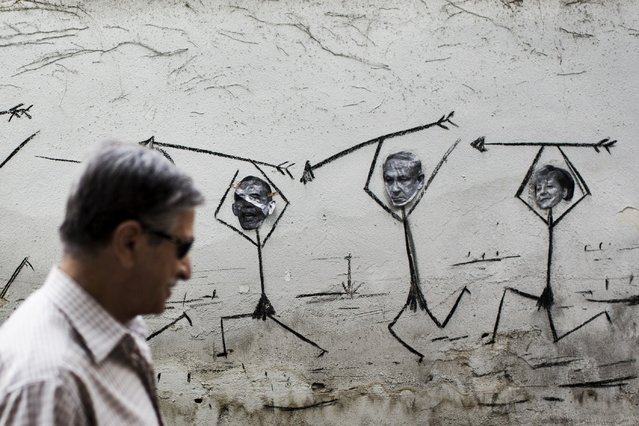 An Iranian man walks past a mural drawing of spearmen bearing the faces of (From L to R): US President Barack Obama, Israeli Prime Minister Benjamin Netanyahu and German Chancellor Angela Merkel on a street in the Iranian capital Tehran on July 30, 2014. (Photo by Behrouz Mehri/AFP Photo)