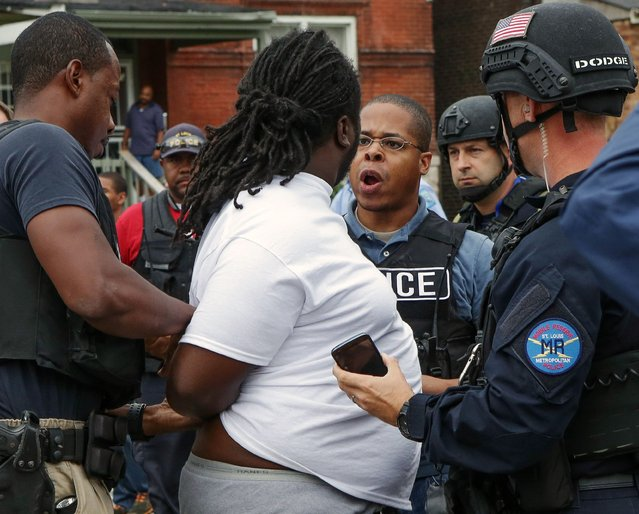 A police officer and a protester have a confrontation during an arrest after a shooting incident in St. Louis, Missouri August 19, 2015. (Photo by Lawrence Bryant/Reuters)