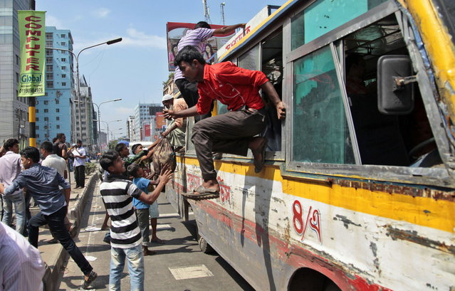 Bangladeshi passengers jump out of the windows of a bus that was attacked during clashes between garment workers and police in Dhaka, Bangladesh, Thursday, August 7, 2014. Bangladesh police on Thursday entered the premises of a garment factory, fired tear gas and used batons to disperse workers who were on a hunger strike since July 28 demanding payment of their salaries and festival allowances. (Photo by A. M. Ahad/AP Photo)