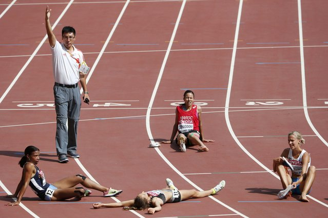 A track official (Top L) calls for a stretcher for Hanane Ouhaddou of Morocco (C) after the women's 3,000 metres steeplechase heat during the 15th IAAF World Championships at the National Stadium in Beijing, China August 24, 2015. (Photo by David Gray/Reuters)