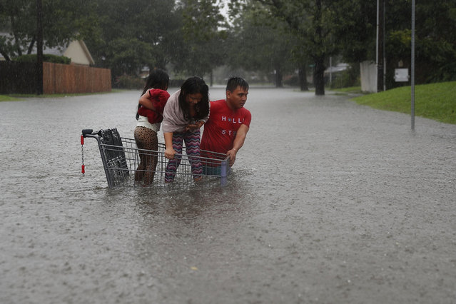A man helps children across a flooded street as they evacuate their home after the area was inundated with flooding from Hurricane Harvey on August 27, 2017 in Houston, Texas. Harvey, which made landfall north of Corpus Christi late Friday evening, is expected to dump upwards to 40 inches of rain in Texas over the next couple of days. (Photo by Joe Raedle/Getty Images)