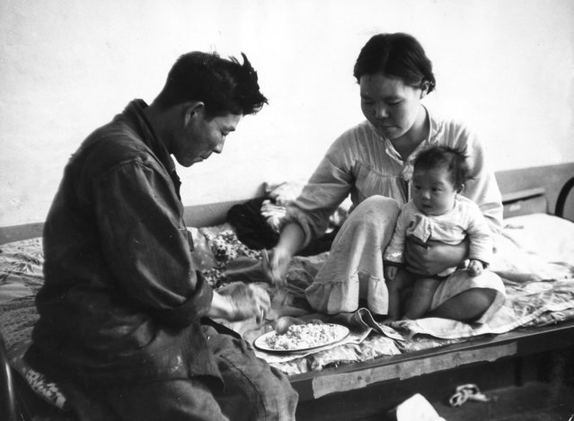 A Korean family share a bowl of rice on a bed in a refugee camp, still homeless nearly five years after the Korean war ended. 23rd July 1955. (Photo by John Chillingworth)