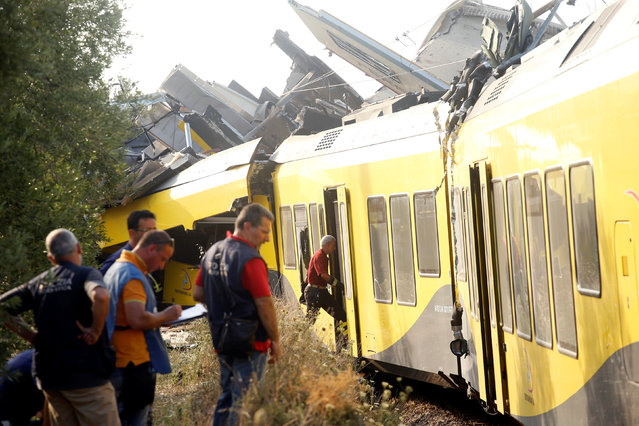 Rescuers stand at the site where two passenger trains collided in the middle of an olive grove in the southern village of Corato, near Bari, Italy, July 12, 2016. (Photo by Alessandro Garofalo/Reuters)