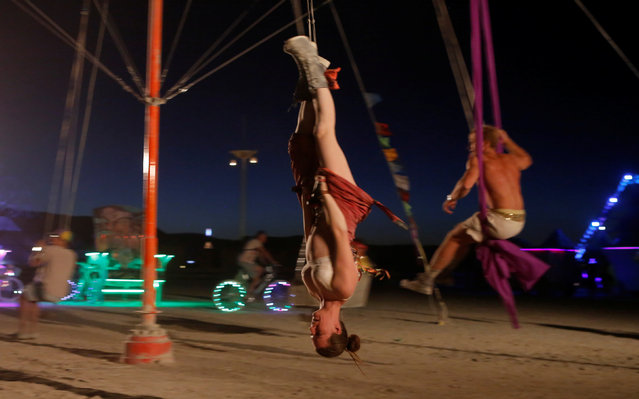 A participant rides a swing as approximately 70,000 people from all over the world gathered for the annual Burning Man arts and music festival in the Black Rock Desert of Nevada, U.S. August 29, 2017. (Photo by Jim Urquhart/Reuters)