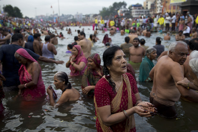 An Indian woman devotee performs rituals as others take holy dips in the Godavari River during Kumbh Mela, or Pitcher Festival, in Nasik, India, Wednesday, August 26, 2015. (Photo by Tsering Topgyal/AP Photo)